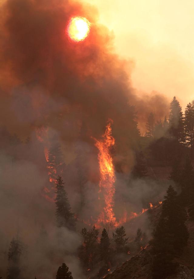 Fire descends a ridge towards homes on the more than 90,000-acre Elk Complex Fire near Pine, Idaho, on Monday Aug. 12, 2013. Thunderstorms threatened more trouble Tuesday for crews battling the fast-moving wildfire. (AP Photo/Times-News, Ashley Smith) MANDATORY CREDIT