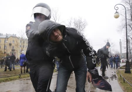 An Interior Ministry officer detains a participant of an opposition protest, calling for Russian President Vladimir Putin not to run for another presidential term next year, in St. Petersburg, Russia, April 29, 2017. REUTERS/Anton Vaganov