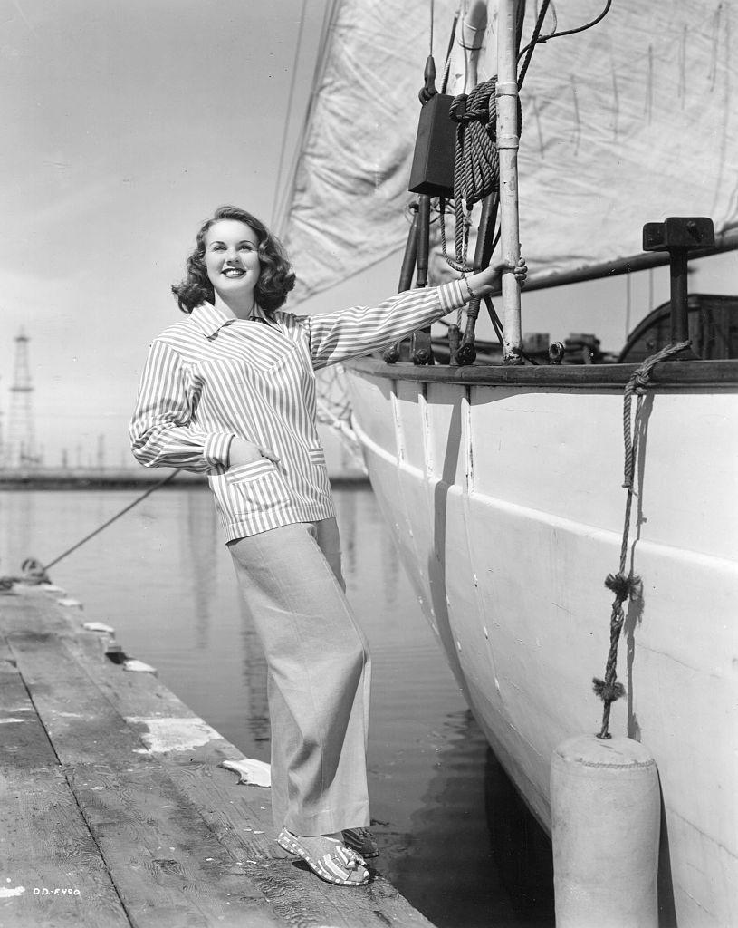 <p>Actress and model Deanna Durbin perfecting a chic sailing look in wide-leg khakis and a striped jacket. </p>