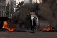 A man rides his scooter through the smoke of burning tires, that were set on fire by protesters to block a road, in Beirut, Lebanon, Thursday, March 4, 2021. Lebanon has been hit by one crisis after another, with widespread protests against the country's corrupt political class breaking out in October 2019. (AP Photo/Bilal Hussein)