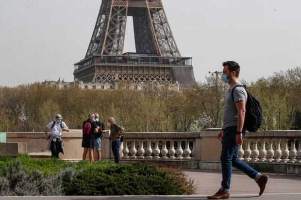 A man wearing a mask crosses the Bir Hakeim bridge in Paris, with the Eiffel Tower in the background, on April 1, 2021. U.S. tourists may be able to visit EU countries this summer if they are fully vaccinated.