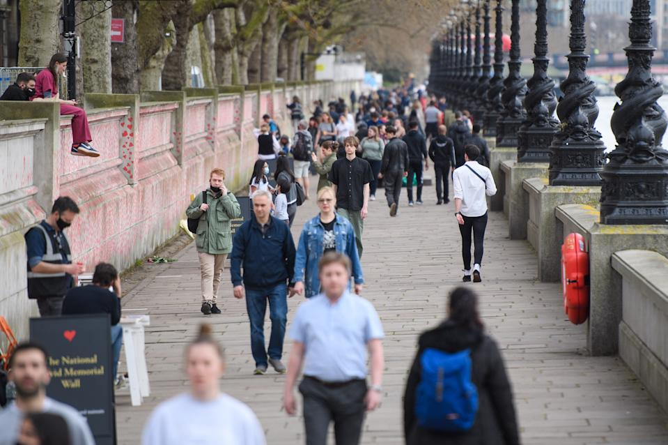 People walk past the COVID-19 Memorial Wall on the Embankment, central London, which has been painted with hearts in memory of the more than 145,000 people who have died in the UK from coronavirus. Picture date: Wednesday March 31, 2021. Photo credit should read: Matt Crossick/Empics