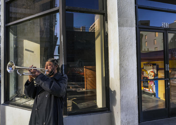 """FILE - In this Feb. 5, 2021, file photo, street musician Roberto Hernandez, originally from El Salvador, plays """"Lambada"""" on his trumpet outside Buddy's, a restaurant temporarily closed due to the COVID-19 pandemic, in downtown Los Angeles. Los Angeles County could move into the next phase of reopening with fewer restrictions as early as next week, though any actual lifting of coronavirus-related constraints would not happen immediately, health officials said Wednesday, March 3, 2021. (AP Photo/Damian Dovarganes, File)"""