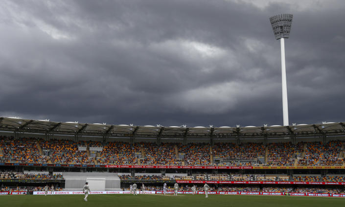 Players watch as rain clouds gather during play on day two of the fourth cricket test between India and Australia at the Gabba, Brisbane, Australia, Saturday, Jan. 16, 2021. (AP Photo/Tertius Pickard)