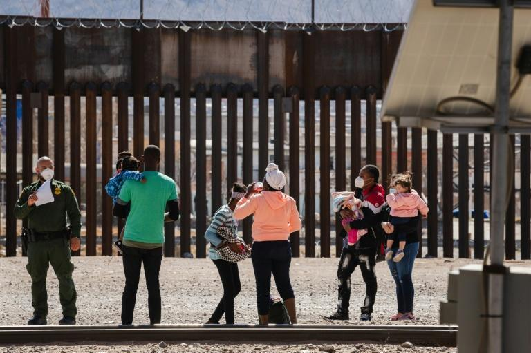 US Border Patrol agents with a group of migrants near downtown El Paso, Texas, on the border with Mexico on March 15, 2021