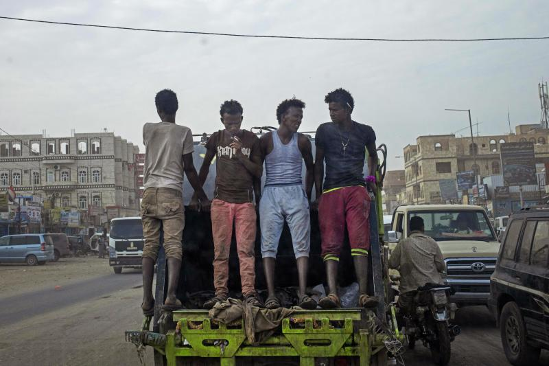 In this July 29, 2019 photo, African migrants make their way to work in Marib, Yemen. In the evenings, thousands of migrants mill around the streets of Marib, one of the main city stopovers on the migrants' route through Yemen. In the mornings, they search for day jobs. They could earn about a dollar a day working on nearby farms. A more prized job is with the city garbage collectors, paying $4 a day. (AP Photo/Nariman El-Mofty)