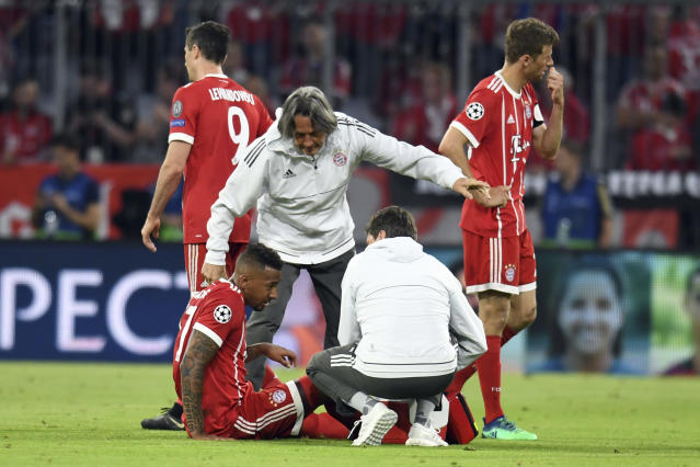Bayern's Jerome Boateng is attend to by team doctor Hans-Wilhelm Mueller-Wohlfahrt during the soccer Champions League first leg semifinal soccer match between FC Bayern Munich and Real Madrid in Munich, southern Germany, Wednesday, April 25, 2018. (Sven Hoppe/dpa via AP)