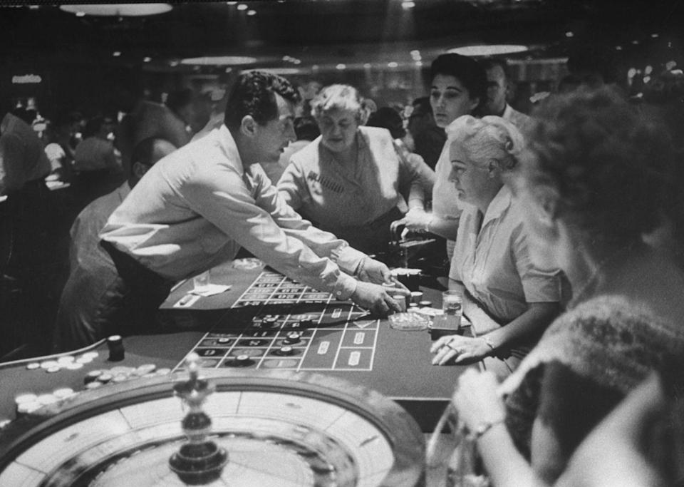 """<p>Dean Martin deals at a casino in 1958. He was a member of the """"Rat Pack,"""" which was made up of a group of entertainers that performed in Las Vegas at casinos.</p>"""
