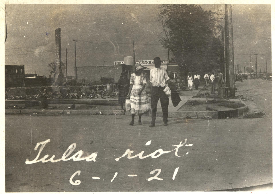 An African American couple walking across a street with smoke rising in the distance after the Tulsa Race Massacre, Tulsa, Oklahoma, June 1921. (Photo: Getty Images)