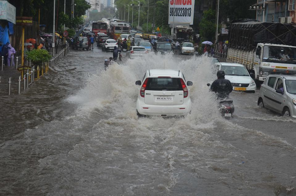 Vehicles brave their way out of flooded road during a heavy monsoon rainfall in Mumbai. (Photo by Arun Patil)