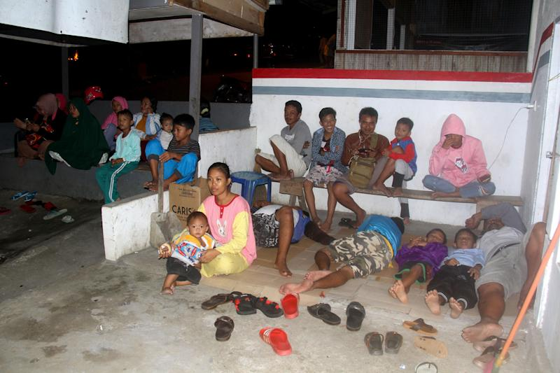 Indonesian families gather outside their home following the earthquake.