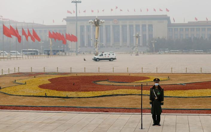 A paramilitary police officer stands guard on Tiananmen Square shrouded in smog - CARLOS GARCIA RAWLINS/REUTERS