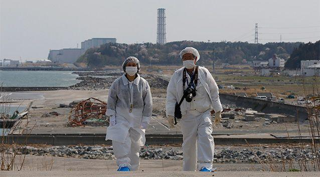 Kazuhiro Onuki, right, and his wife, Michiko, wearing white protective gears and filtered masks, walk along the coast damaged by the 2011 tsunami against a backdrop of Fukushima Dai-ni Nuclear Power Plant, that stands south of the crippled Fukushima Dai-ichi nuclear plant. Photo: AP.