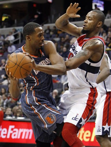 Charlotte Bobcats forward Derrick Brown, left, tries to pass to a teammate under pressure from Washington Wizards forward Rashard Lewis, right, during the first quarter of an NBA basketball game in Washington, Wednesday, Jan. 25, 2012. (AP Photo/Ann Heisenfelt)