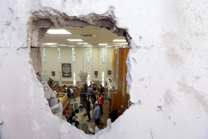 People clean inside a synagogue damaged by a rocket fired by Palestinian militants in the Gaza Strip, as Israeli-Palestinian cross-border violence continues, in Ashkelon, southern Israel, May 16, 2021. / Credit: BAZ RATNER/REUTERS