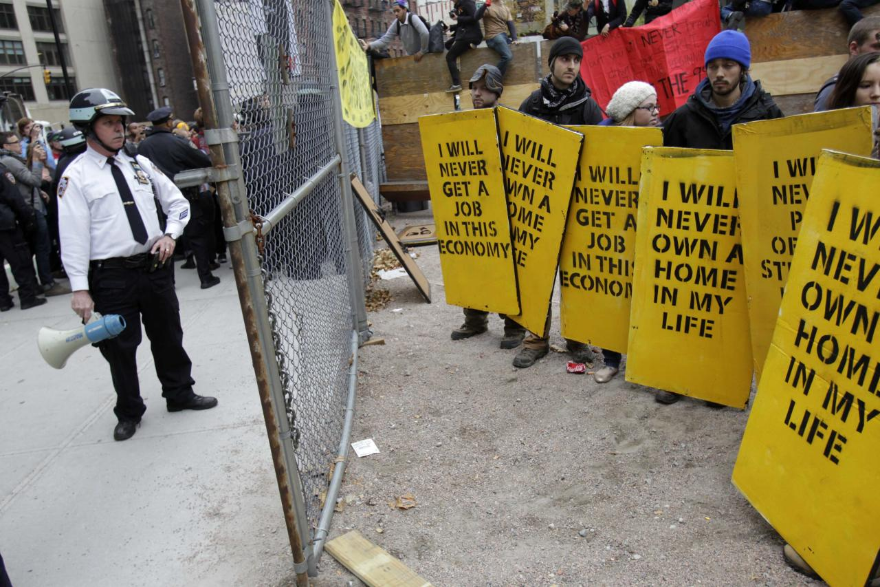 Occupy Wall Street protesters face off with police officers on the edge of a gated park in New York, Tuesday, Nov. 15, 2011. The protesters eventually left the private property after police entered the park and made arrests. (AP Photo/Seth Wenig)