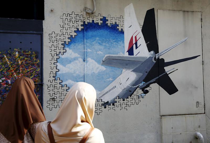Women look at a mural of missing Malaysia Airlines flight MH370 two years after it disappeared, in Kuala Lumpur, Malaysia