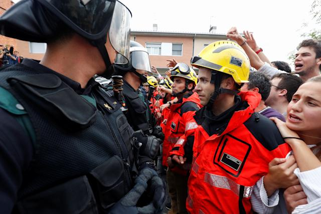 Firemen and people face off Spanish Civil Guard officers outside a polling station for the banned independence referendum in Sant Julia de Ramis, Spain Oct. 1, 2017.