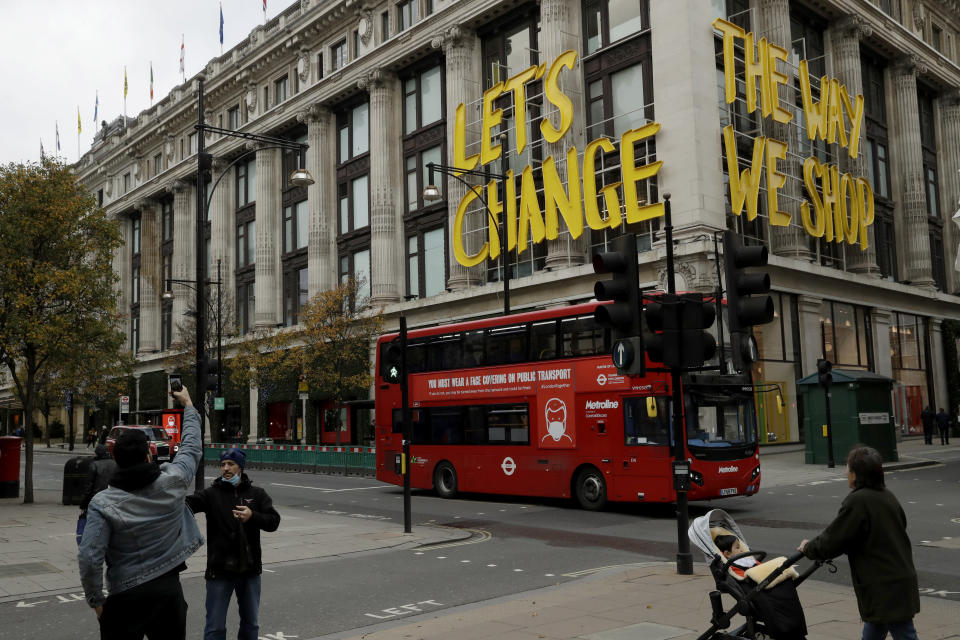 """The words """"Let's Change The Way We Shop"""" are displayed on the Selfridges department store on Oxford Street, which is temporarily closed for in-store browsing with online collection possible from a collection point, during England's second coronavirus lockdown, in London, Monday, Nov. 23, 2020. British Prime Minister Boris Johnson has announced plans for strict regional measures to combat COVID-19 after England's second lockdown ends Dec. 2, sparking a rebellion by members of his own party who say the move may do more harm than good. (AP Photo/Matt Dunham)"""
