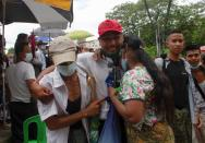 A released prisoner reacts with his relatives outside the Insein prison in Yangon