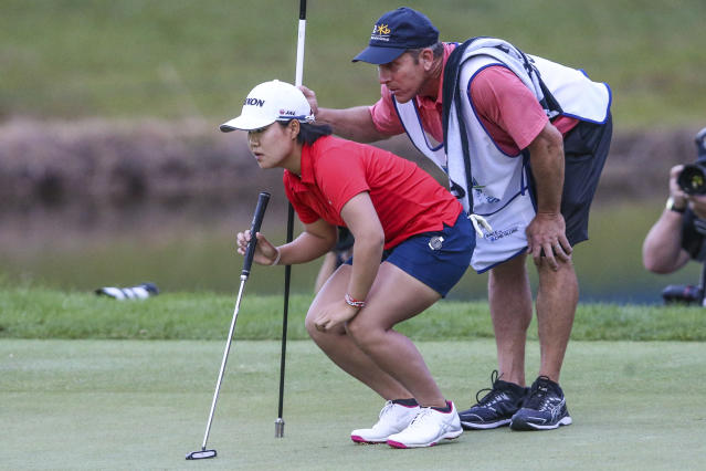 Nasa Hataoka, left, of Japan, and her caddie Greg Johnston look over the 18th green before putting during the final round of the Tournament of Champions LPGA golf tournament Sunday, Jan. 19, 2020, in Lake Buena Vista, Fla. (AP Photo/Gary McCullough)