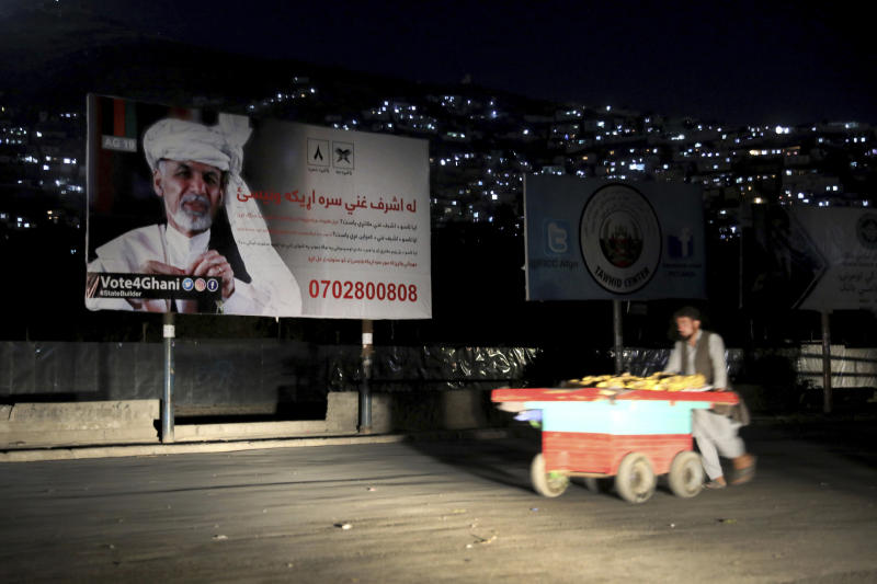 In this Sept. 9, 2019, photo, an Afghan street vendor pulls his hand cart in front of an election poster of Afghan President Ashraf Ghani, who seeks a second term, in Kabul, Afghanistan. President Donald Trump's sudden halt to U.S.-Taliban talks looks like a gift to the beleaguered Afghan president, who has insisted on holding a key election in less than three weeks' time despite widespread expectations that a peace deal would push it aside. (AP Photo/Ebrahim Noroozi)