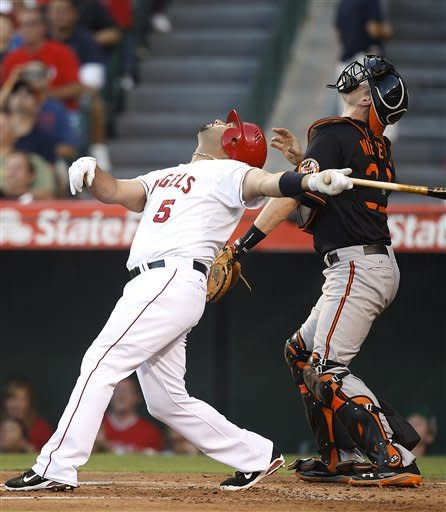 Los Angeles Angels' Albert Pujols, left, and Baltimore Orioles catcher Matt Wieters look at a foul ball hit by Pujols in the first inning of a baseball game in Anaheim, Calif., Friday, July 6, 2012. (AP Photo/Jae C. Hong)