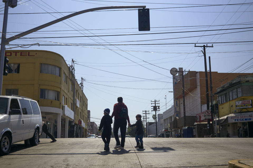 In this March 5, 2019, image, Ruth Aracely Monroy walks with her sons in Tijuana, Mexico. After requesting asylum in the United States, the family was returned to Tijuana to wait for their hearing in San Diego. They were one of the first families to contend with a new policy that makes asylum seekers stay in Mexico while their cases wind through U.S. immigration courts. (AP Photo/Gregory Bull)
