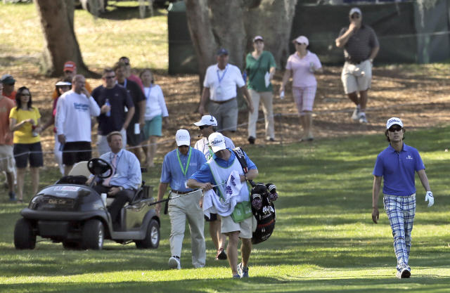 PGA Tour official Gary Young, left, in cart, follows Kevin Na, right, down the 10th fairway during the third round of the Valspar Championship golf tournament at Innisbrook Saturday, March 15, 2014, in Palm Harbor, Fla. Officials were concerned over slow play. (AP Photo/Chris O'Meara)