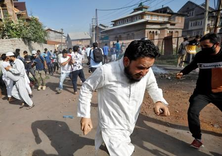 Kashmiris run for cover as Indian security forces fire teargas shells during clashes, after scrapping of the special constitutional status for Kashmir by the Indian government, in Srinagar