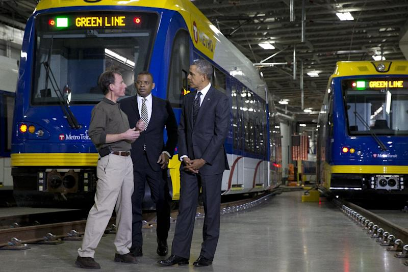 Mark Fuhrmann, New Start Program Director of Metro Transit, left, talks with President Barack Obama and Transportation Secretary Anthony Foxx, during a tour of the Metro Transit Light Rail Operations and Maintenance Facility in St. Paul, Minn., Wednesday, Feb. 26, 2014. In Minnesota Obama is expected to speak at Union Depot rail and bus station with a proposal asking Congress for $300 billion to update the nation's roads and railways, and about a competition to encourage investments to create jobs and restore infrastructure as part of the President's Year of Action. (AP Photo/Jacquelyn Martin)