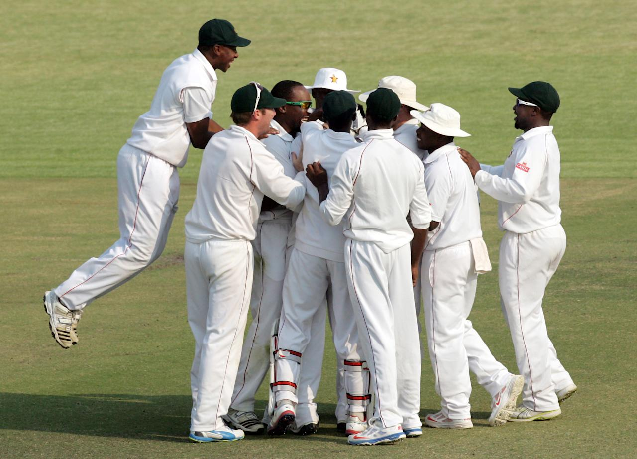 Zimbabwe's players celebrate after taking a wicket on the fourth day of the second test match between Pakistan and Zimbabwe at the Harare Sports Club on September 13, 2013. AFP PHOTO / JEKESAI NJIKIZANA        (Photo credit should read JEKESAI NJIKIZANA/AFP/Getty Images)