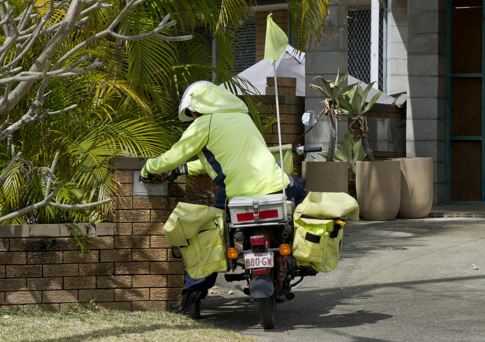 An Australia Post employee is seen delivering mail on a residential street on the Gold Coast.