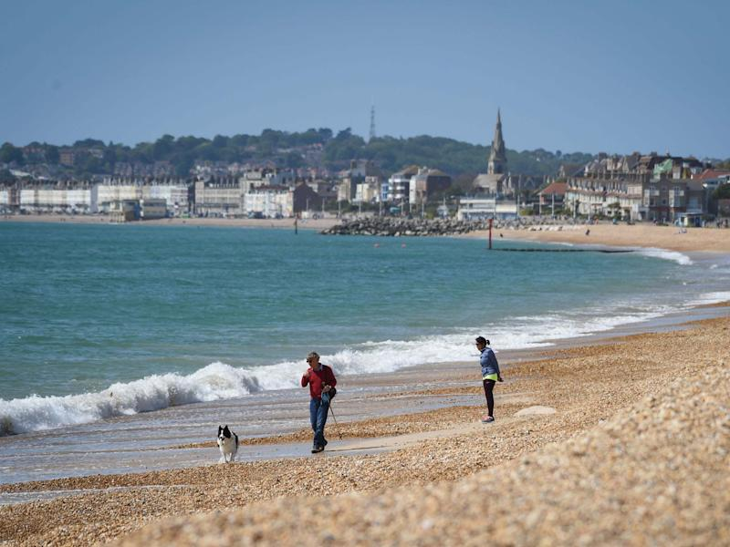A man walks his dog on Preston beach in Weymouth: Getty Images