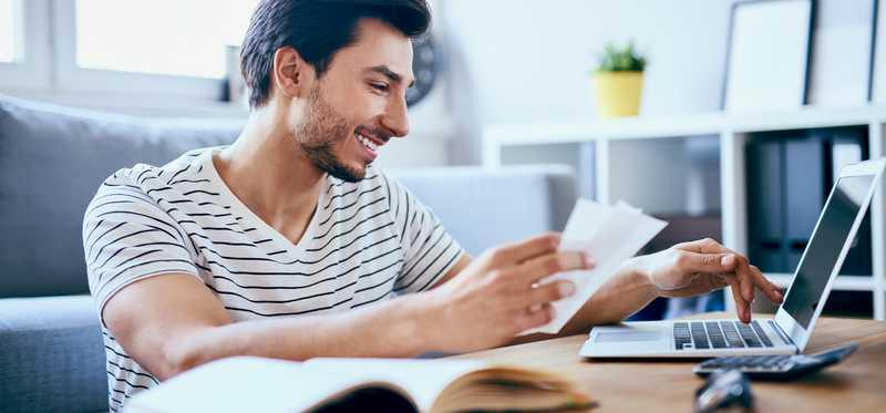 A man smiles as he pays bills online.