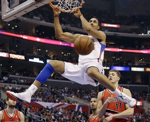 Los Angeles Clippers center Ryan Hollins (15) dunks over Portland Trail Blazers center Meyers Leonard (11) in the first half of an NBA basketball game in Los Angeles, Tuesday, April 16, 2013. (AP Photo/Reed Saxon)