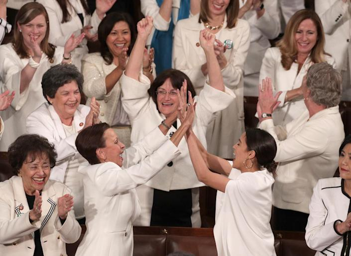 WASHINGTON, DC - FEBRUARY 05: Rep. Alexandria Ocasio-Cortez (D-NY) and other female lawmakers cheer during President Donald Trump's State of the Union address in the chamber of the U.S. House of Representatives at the U.S. Capitol Building on February 5, 2019 in Washington, DC. A group of female Democratic lawmakers chose to wear white to the speech in solidarity with women and a nod to the suffragette movement. (Photo by Alex Wong/Getty Images)