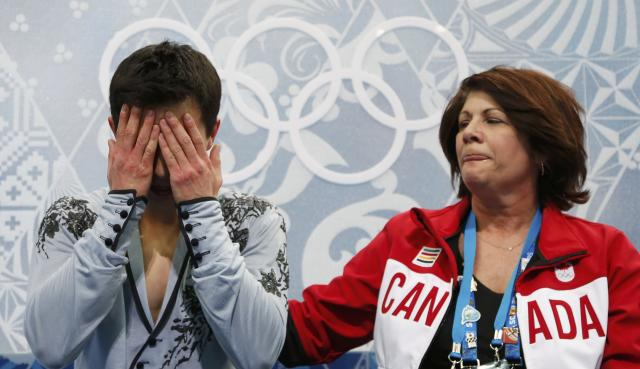 "Canada's Patrick Chan reacts with his coach Kathy Johnson in the ""kiss and cry"" area during the Figure Skating Men's Free Skating Program at the Sochi 2014 Winter Olympics, February 14, 2014. REUTERS/Lucy Nicholson (RUSSIA - Tags: OLYMPICS SPORT FIGURE SKATING TPX IMAGES OF THE DAY)"