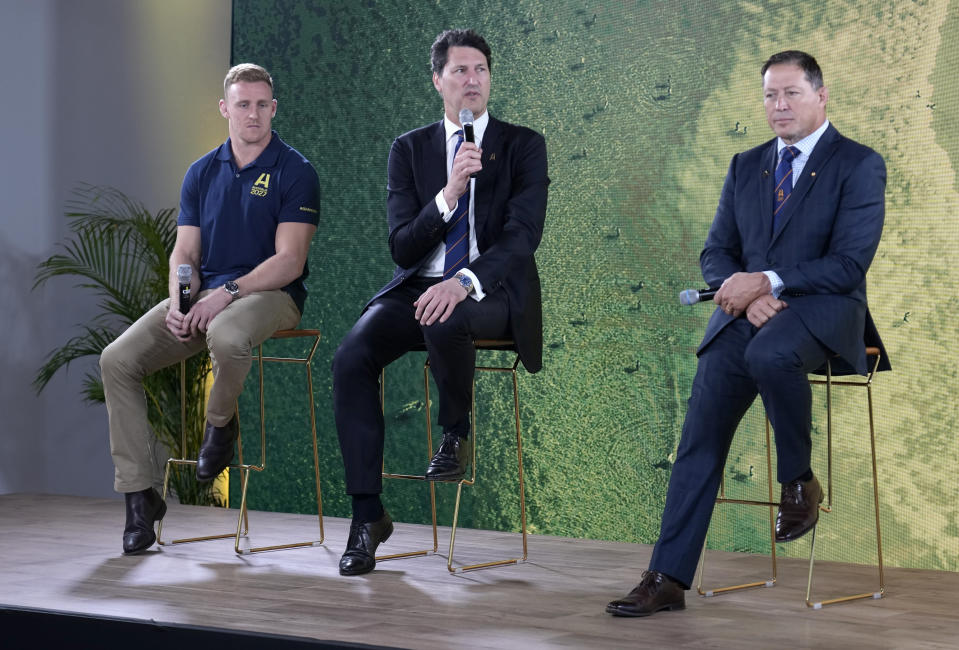Former Australian rugby Rugby World Cup winning captain John Eales, center, sits with former captain Phil Kearns, right, and current player Reece Hodge as they answer questions at a media event in Sydney where Australia formally announced its bid to host the 2027 Rugby World Cup, Thursday, May 20, 2021. It would be the third time the sport's showcase event would be held in the country. (AP Photo/Mark Baker)