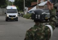 A soldier signals an ambulance as it drives towards the military base where a car bomb exploded in Cucuta, Colombia, Tuesday, June 15, 2021. Colombian authorities still have not confirmed how many were injured in the explosion. (AP Photo/Ferley Ospina)