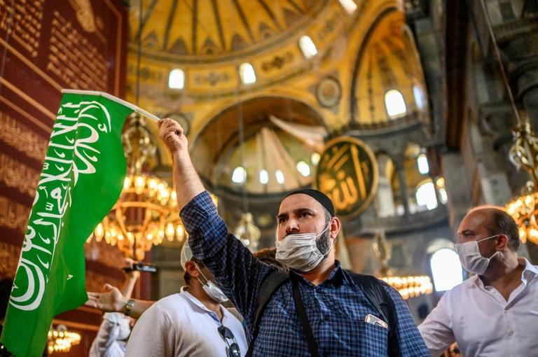 A worshipper holds an Islamic flag inside the mosque