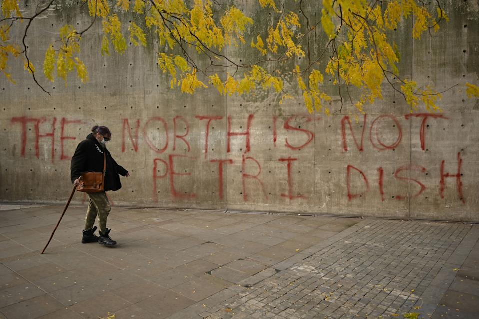 """A woman wearing a face-mask walks past graffiti declaring that 'the north is not a petri dish' after Greater Manchester mayor Andy Burnham threatened legal action if Tier 3 restrictions are imposed on the city without agreement, in Picadilly Gardens, central Manchester on October 16, 2020, as the number of cases of the novel coronavirus COVID-19 rises. - The government on Thursday announced more stringent measures but as ministers tightened the screw on social interaction to cut close-contact transmission, they sparked a furious row with leaders in northwest England, where infection rates are highest. Greater Manchester Mayor Andy Burnham accused the government of being """"willing to sacrifice jobs and businesses here to try and save them elsewhere"""". (Photo by Oli SCARFF / AFP) (Photo by OLI SCARFF/AFP via Getty Images)"""