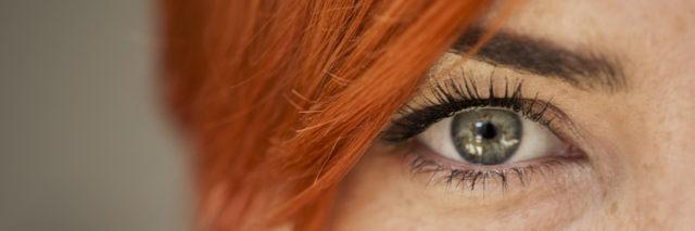 close up shot of a woman's green eye looking at the camera with red haired bangs over her face