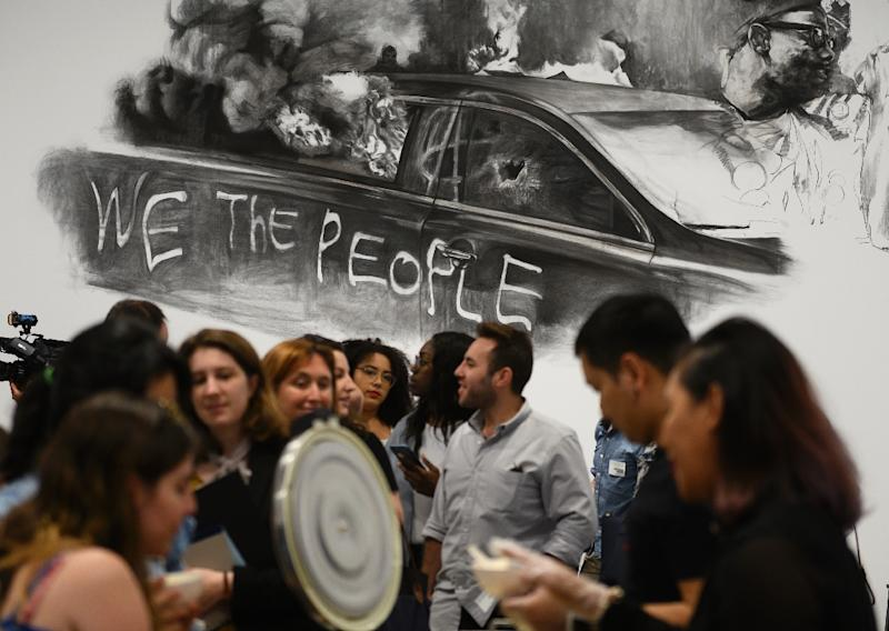 People wait for Thai curry on rice in Tiravanija's interactive installation at the Hirshhorn Museum and Sculpture Garden, against the backdrop of a drawing of a car set on fire during US President Donald Trump's January 20, 2017 inauguration (AFP Photo/ANDREW CABALLERO-REYNOLDS)