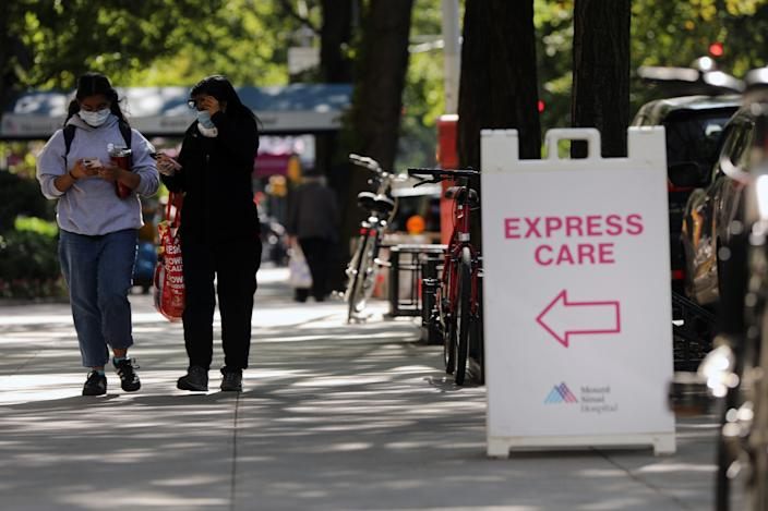 "NEW YORK, NEW YORK - SEPTEMBER 22: People walk past an ""Express Care"" sign at Mount Sinai Hospital in Manhattan, which has treated hundreds of COVID-19 patients since March, on September 22, 2020 in New York City. While New York's infection rate is currently below one percent,  the U.S. has reported more than 6.7 million confirmed cases and 200,000 deaths attributed to COVID-19, making it the world leader in both. (Photo by Spencer Platt/Getty Images)"