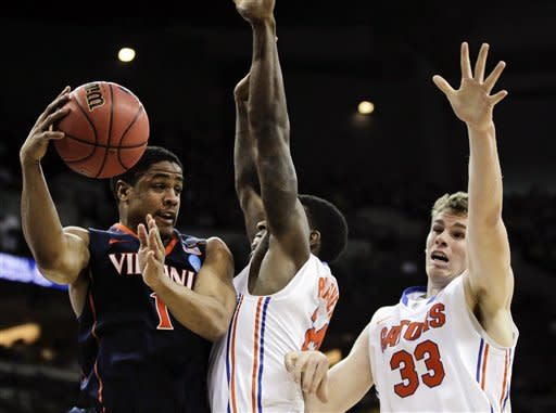 Virginia's Jontel Evans, left, passes around the defense of Florida's Casey Prather and Erik Murphy (33) during the first half of an NCAA tournament second-round college basketball game at CenturyLink Center in Omaha, Neb., Friday, March 16, 2012. (AP Photo/Nati Harnik)