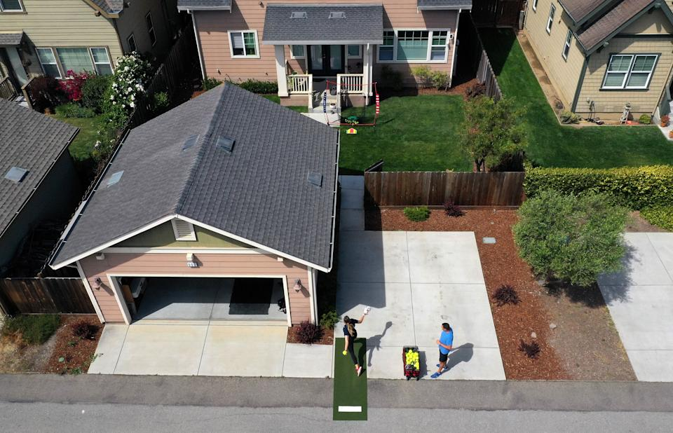 SALINAS, CALIFORNIA - JUNE 02:  In this aerial view from a drone, Olympic softball pitcher Monica Abbott practices by pitching through an open door in a fence to a net in her backyard during a training session on June 02, 2020 in Salinas, California.  Abbott was on the United States team at the 2008 Olympics that won the silver medal, and was on the 2007 and 2019 United States teams that won gold medals at the Pan American Games.  She also holds the NCAA career records for most victories, shutouts, and strikeouts. Athletes across the globe are now training in isolation under strict policies in place due to the Covid-19 pandemic.  (Photo by Ezra Shaw/Getty Images)