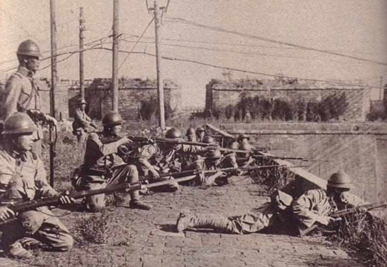 Japanese soldiers standing and lying pointing guns.