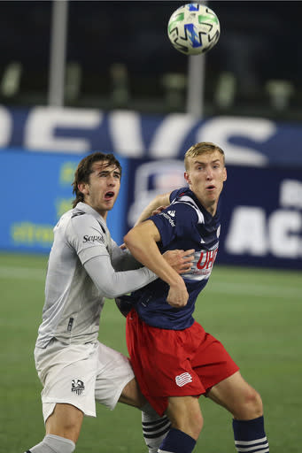Montreal Impact defender Luis Binks, left, and New England Revolution forward Adam Buksa watch the ball during the first half of an MLS soccer matc Friday, Nov. 20, 2020, in Foxborough, Mass. (AP Photo/Stew Milne)
