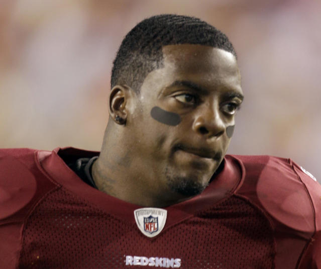 FILE - This Sept. 12, 2010, file photo shows Washington Redskins running back Clinton Portis before the start of an NFL football game against the Dallas Cowboys, in Landover, Md. Ten former NFL players have been charged with defrauding the leagues healthcare benefit program. They include five who played on the Washington Redskins, including Clinton Portis and Carlos Rogers. (AP Photo/Rob Carr, File)